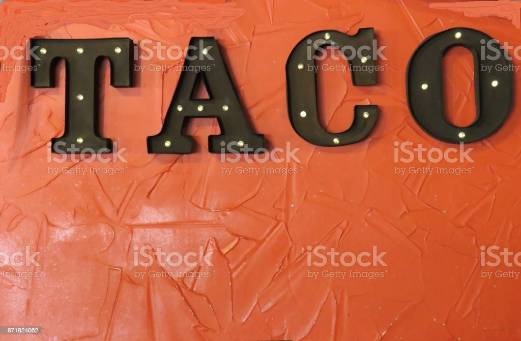 Taco sign Taco sign on an orange background Food And Drink Industry Stock Photo