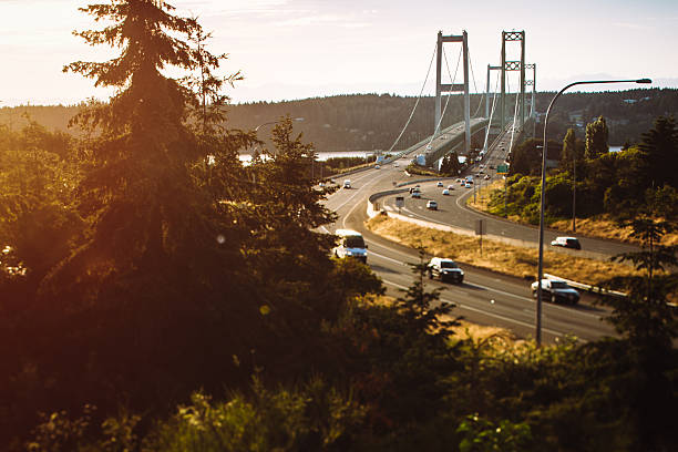 Tacoma Narrow Bridge An image of cars crossing the Tacoma Narrows Bridge at sunset.  The Tacoma Narrows bridge is actually two twin suspension bridges spanning the Puget Sound, Washington State, USA.  State Route 16 connects to the Kitsap Peninsula and close towns such as Gig Harbor, Port Orchard, and Bremerton. gig harbor stock pictures, royalty-free photos & images
