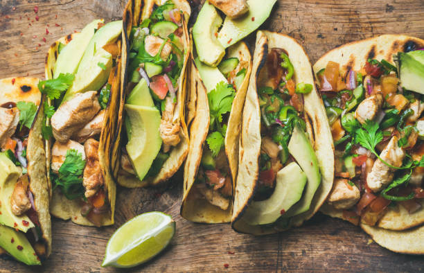 Tacos with grilled chicken, avocado, fresh salsa sauce and limes Tacos with grilled chicken, avocado, fresh salsa sauce and limes over rustic wooden background, top view. Healthy low carb and low fat lunch or food for company. Dieting and weight loss concept taco stock pictures, royalty-free photos & images