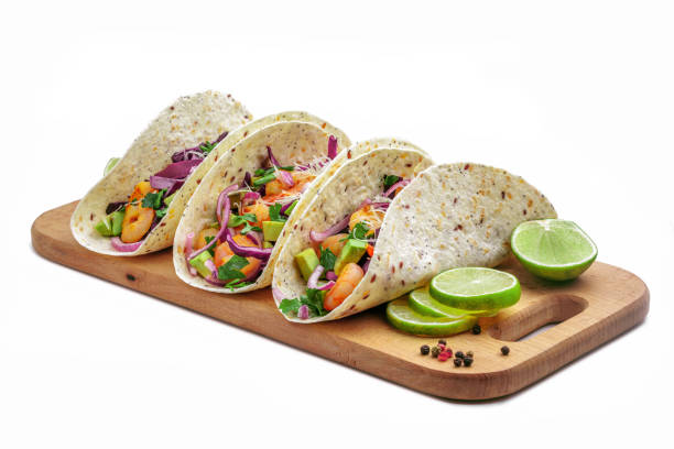 Tacos with shrimp Tacos with shrimps., avocado and red onion on a wooden table. Traditional American fast food. Studio shot, isolated on white background. taco stock pictures, royalty-free photos & images