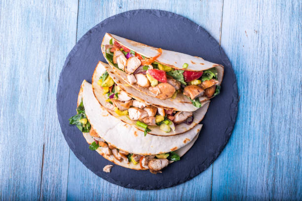 Tacos com vegetais, abacate e peito de galinha em um prato da ardósia-aperitivo mexicano tradicional - foto de acervo