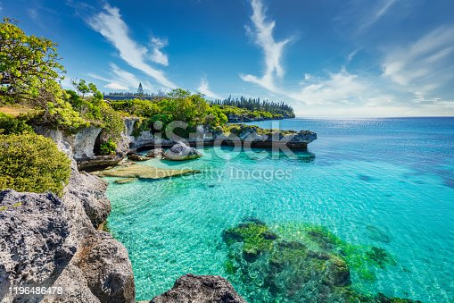 View over turquoise lagoon at Tadine Bay, south-west coast of Maré Island with beautiful natural rocky lagoon and coral reef to the horizon under sunny blue summer sky. Tadine Bay, Mare Island, Loyalty Islands, New Caledonia, Pacific Ocean Islands.