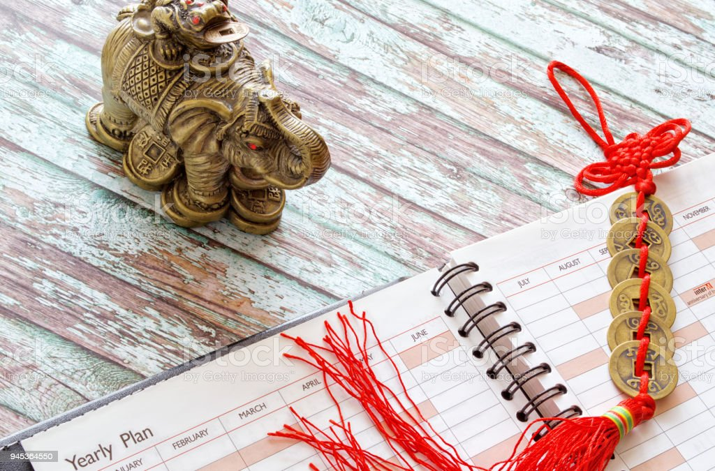 Taditsionny Chinese symbols of wealth: an elephant with a toad on a back; the coins connected by red thread and a modern notebook on a wooden table. stock photo