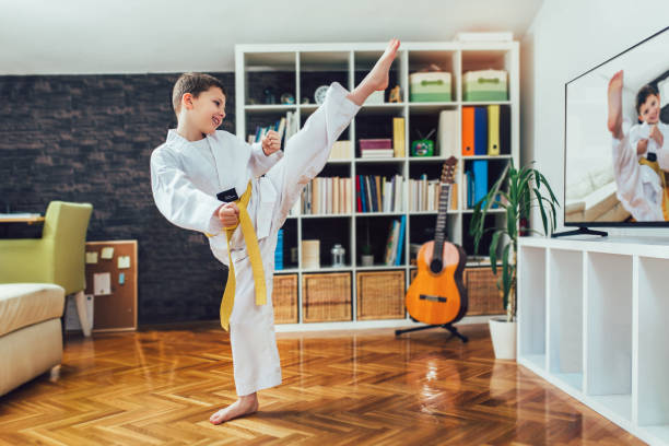 Taekwondo boy exercising at home in living room. stock photo