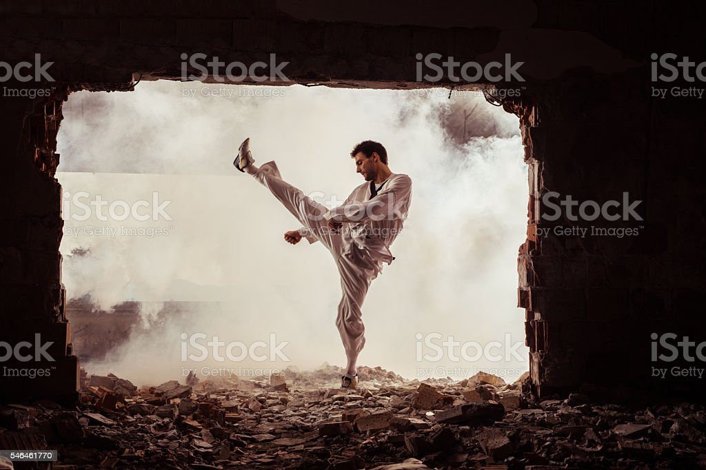 Taekwondo fighter practicing martial arts among ruins. stock photo