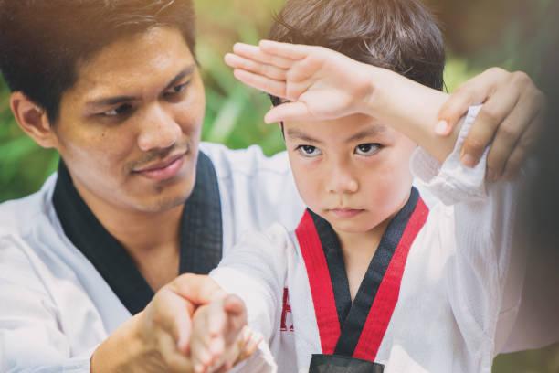 taekwondo meister schwarzgurt unterrichten kid, wache zu kämpfen - asiatischer kampfsport stock-fotos und bilder