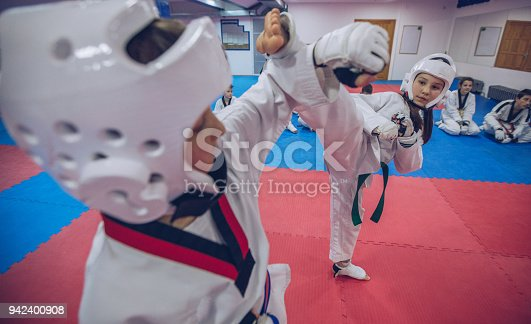 Group of people, taekwondo kids team training indoors, two children fighting.
