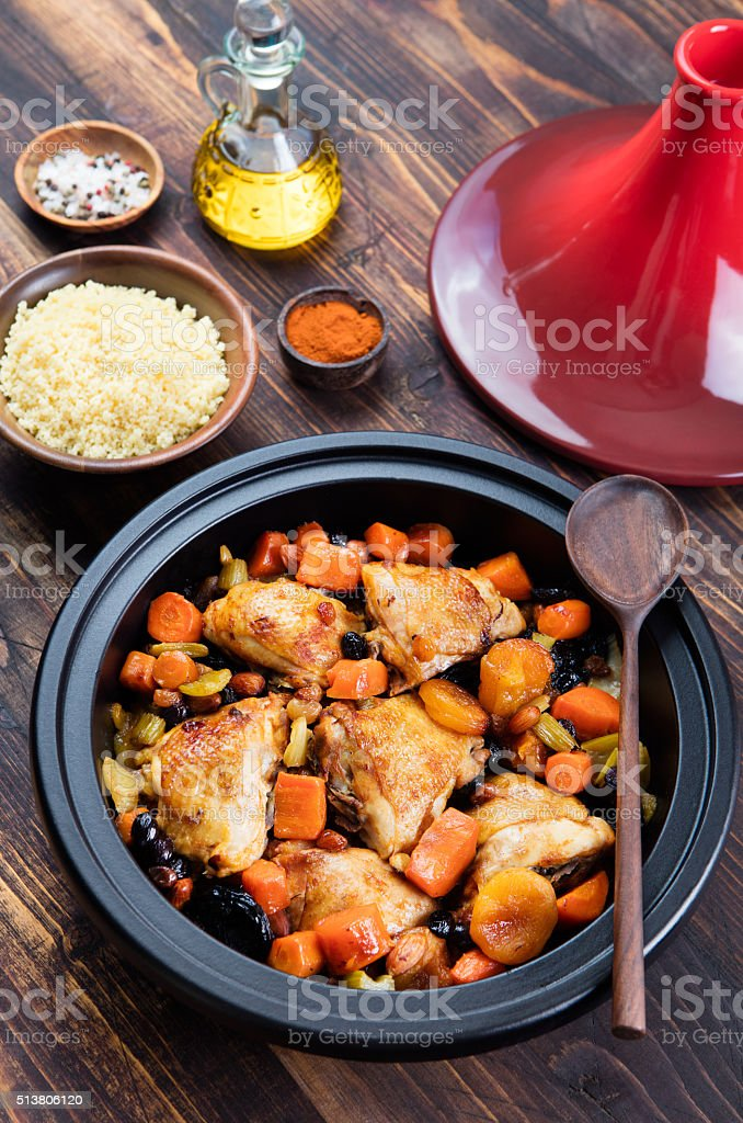 Tagine with cooked chicken and vegetables Wooden background Copy space stock photo