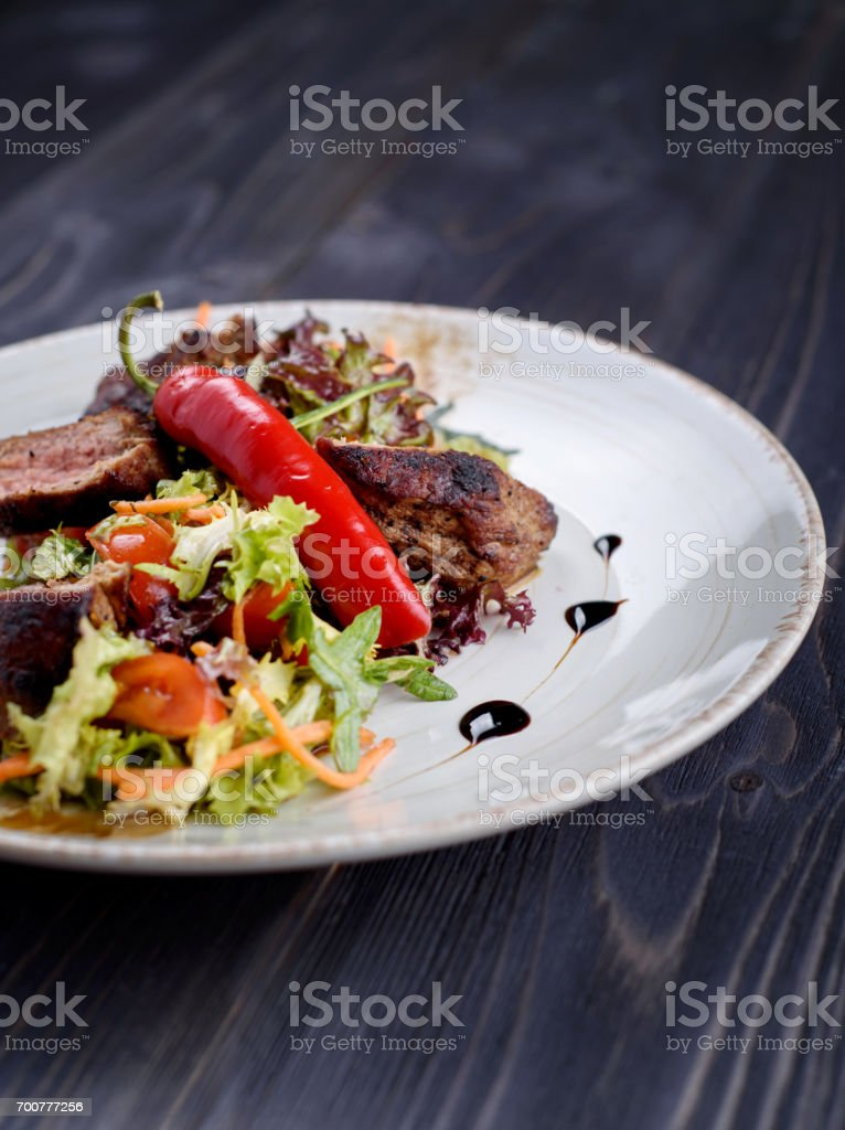 Tagliata of beef with salad on a white plate stock photo