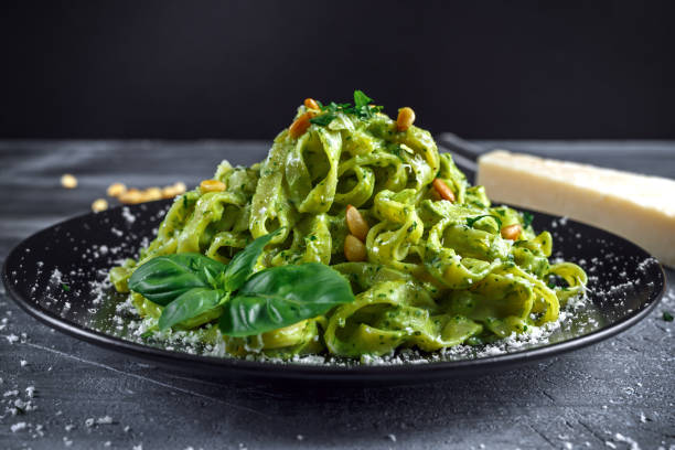 Tagliatelle pasta with pesto sauce, pine nuts and parmesan on black plate. Tagliatelle pasta with pesto sauce, pine nuts and parmesan on black plate tagliatelle stock pictures, royalty-free photos & images