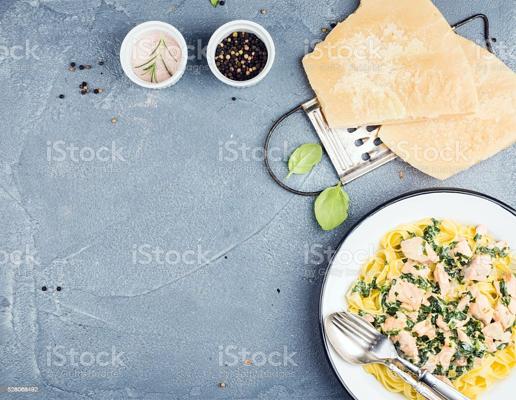 Tagliatelle pasta with salmon, spinach and creamy sauce, parmesan cheese stock photo