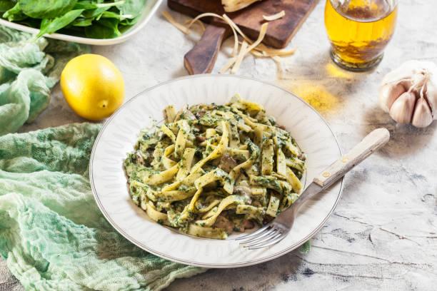 tagliatelle nudeln mit spinat und pilzen auf einem teller - spaghetti mit spinat stock-fotos und bilder