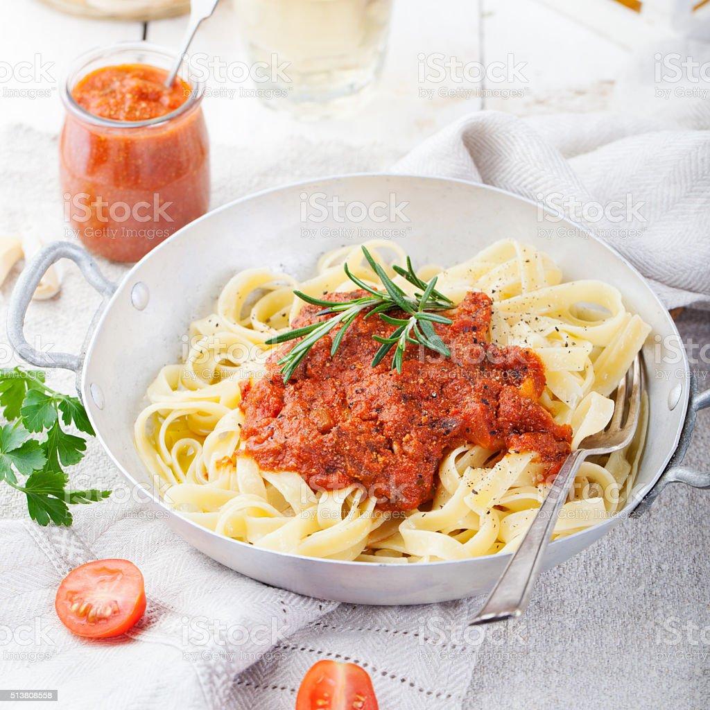 Tagliatelle pasta with tomato sauce and red pesto Italian cuisine stock photo