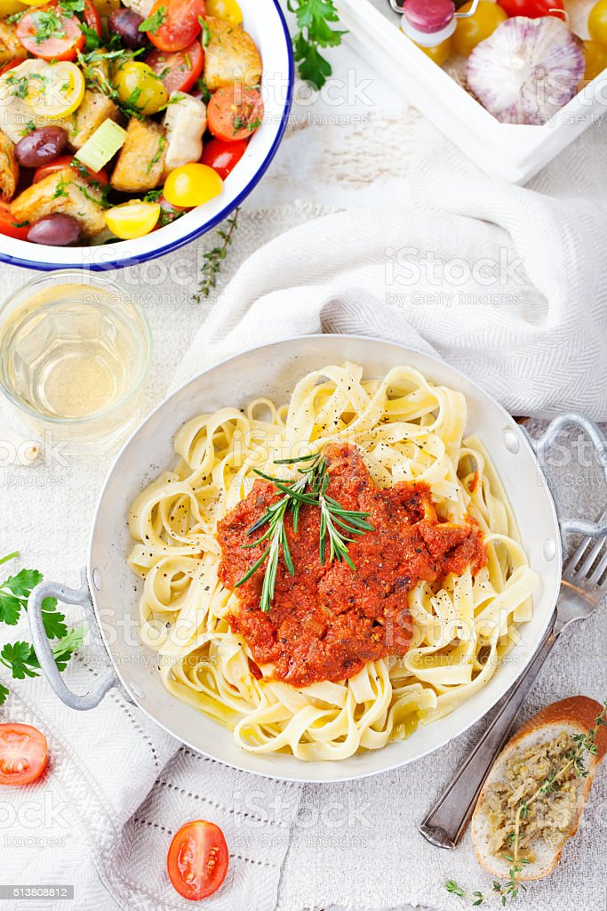 Tagliatelle pasta with tomato sauce and red pesto Top view stock photo