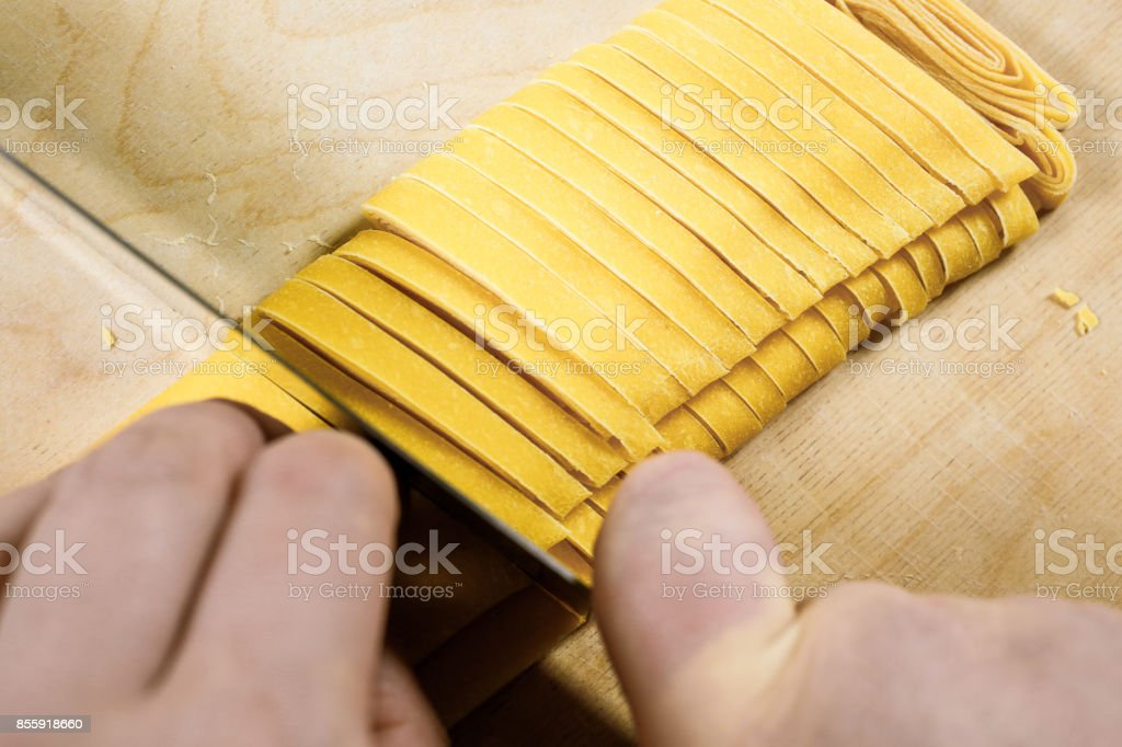 Tagliatelle. Traditional italian fresh ribbon shaped homemade pasta. The moment of cut in the preparation process. stock photo