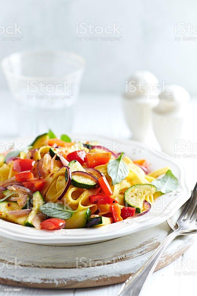 Tagliatelle with zucchini, pepper and red onion stock photo
