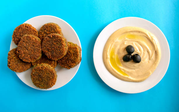 Tahina dipping and falafel on blue background. stock photo