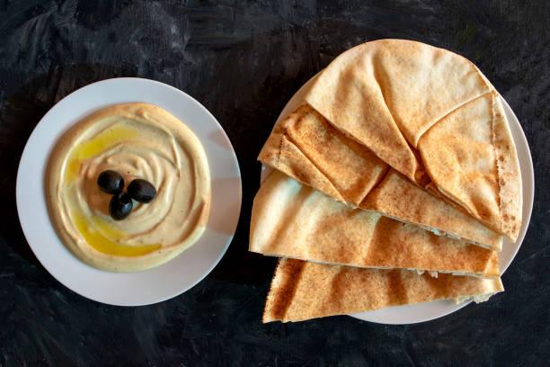 Tahini sauce and pita bread on dark gray rustic background. stock photo