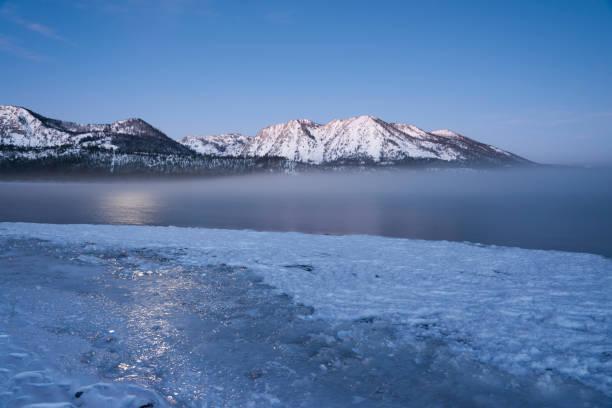 tahoe bei mondschein - lake tahoe winter stock-fotos und bilder