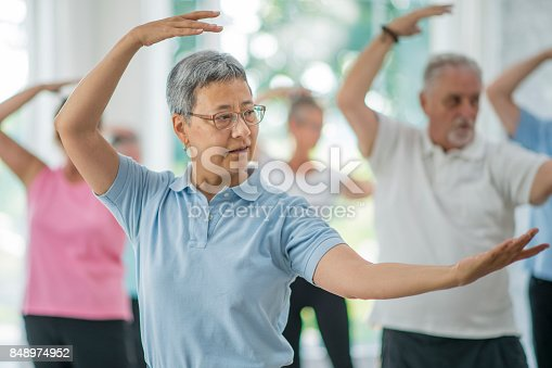 A multi-ethnic group of senior adults are taking a tai chi fitness class. They are practicing their martial art inside of a brightly lit studio. Here, a woman of asian ethnicity is leading the class through movements.