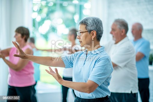 A group of seniors are doing tai chi in a fitness center. They are stretching their arms forwards.