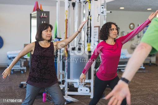 An occupational therapist works with two women in a clinic as he takes them through tai chi exercises. He is in the foreground with his back to the camera. They are standing with their arms extended in front of them.