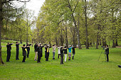 """Oslo, Norway - May 5, 2012: Man photographing a group of people of different age and ethnic origin practicing Qigong or Tai chi in the park at the Royal Norwegian Castle."""