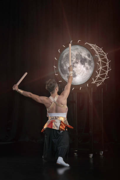 taiko drummer hits the big drum full moon on stage on a black background, back view. elements of this image furnished by nasa. - theatre full of people stage foto e immagini stock