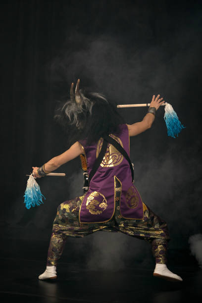 taiko drummer in a wig and a demon mask on stage with drumsticks on a black background. back amd profile full length portrait. demon from japanese mythology. - theatre full of people stage foto e immagini stock