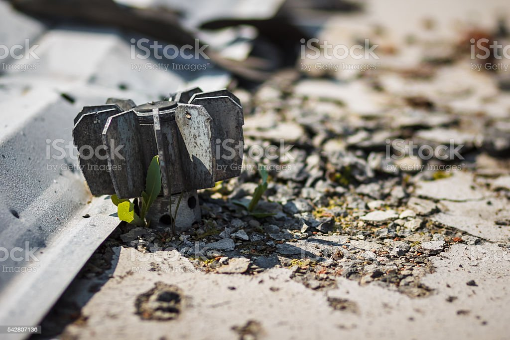 tail of artillery mine with sprouting around grass stock photo
