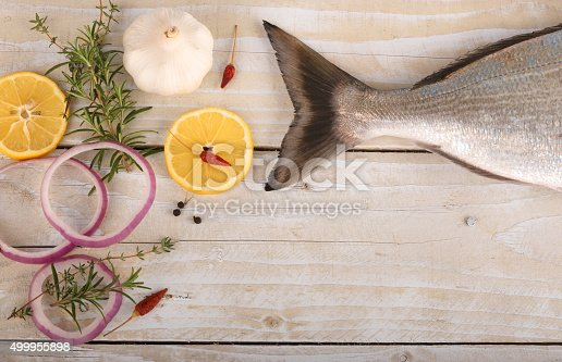 Tail of fresh dorado with spices and vegetables on wooden table