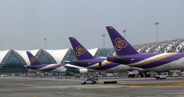 tail of thai airways passenger airplane at suvarnabhumi airport bangkok.thailand - respiratory tract stock photos and pictures