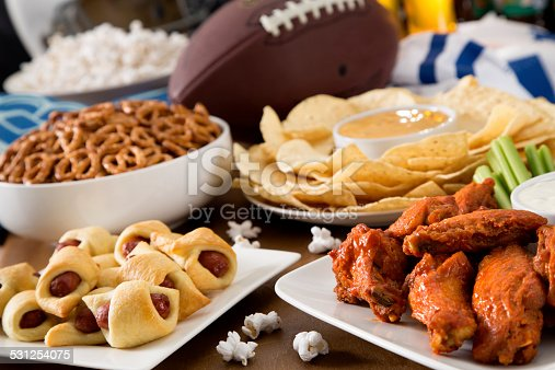 Hot wings, nachos, pigs in a blanket, beer, and popcorn, a tailgate party spread.  Please see my portfolio for other food and drink images.