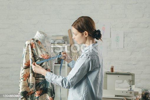 Tailor adjusts garment design on mannequin in workshop - fashion atelier, slow fashion, tailor craft, handmade clothes