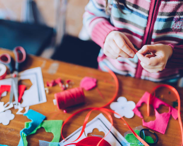 tailor art workshops for children - a girl sewing felt decorations tailor art workshops for children - a girl sewing felt decorations - colorful fabrics lying on a table button sewing item stock pictures, royalty-free photos & images
