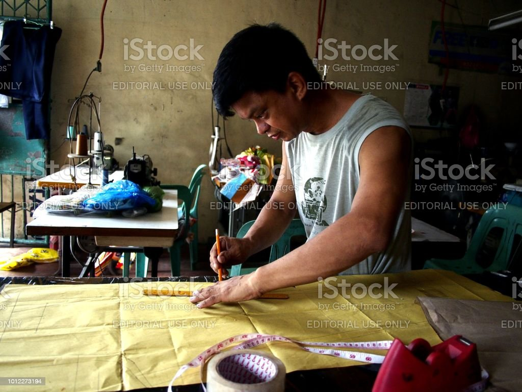 A tailor creates a pattern for a dress at his tailoring shop. stock photo