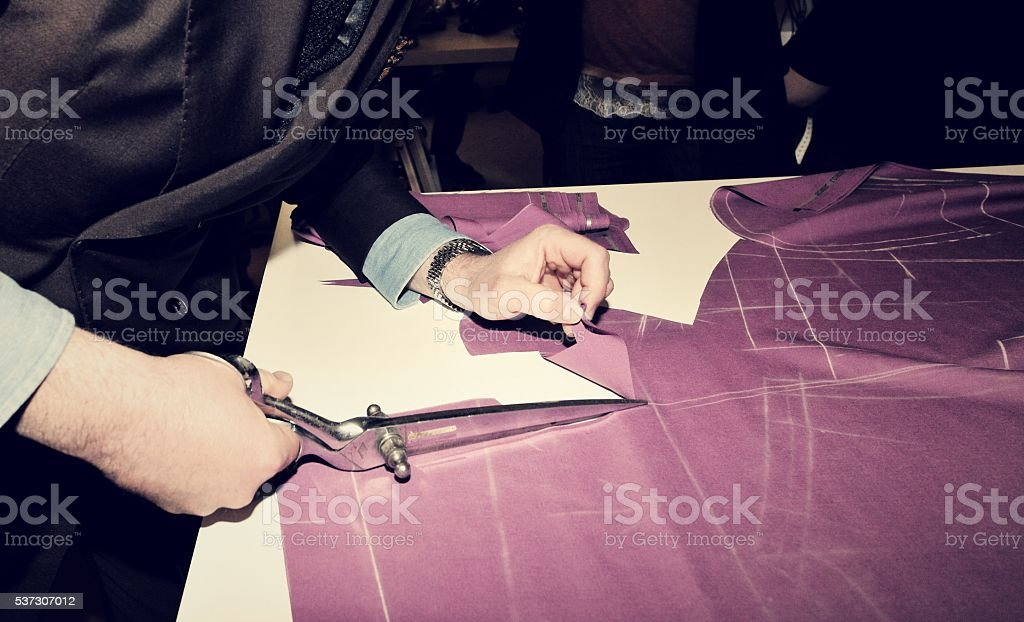 Tailor cutting fabric for bespoke suit stock photo