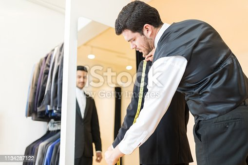istock Tailor Examining Designer Suit At Shop 1134287122