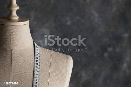 Tailor Mannequin with measure tape in front of dark background.