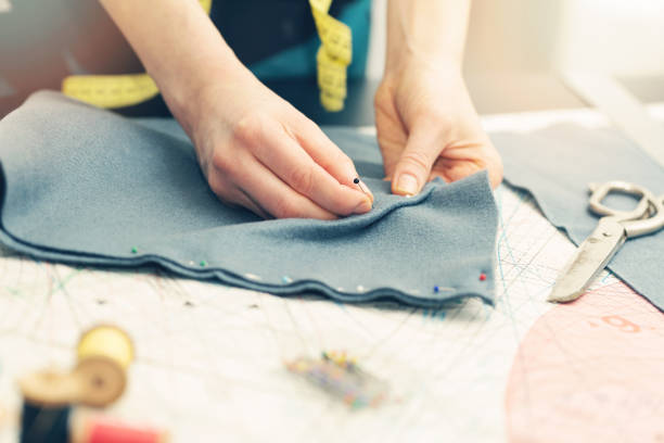 tailor marking the fabric with sewing pins stock photo
