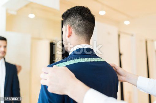 istock Tailor Measuring Customer With Measure Tape 1134289017