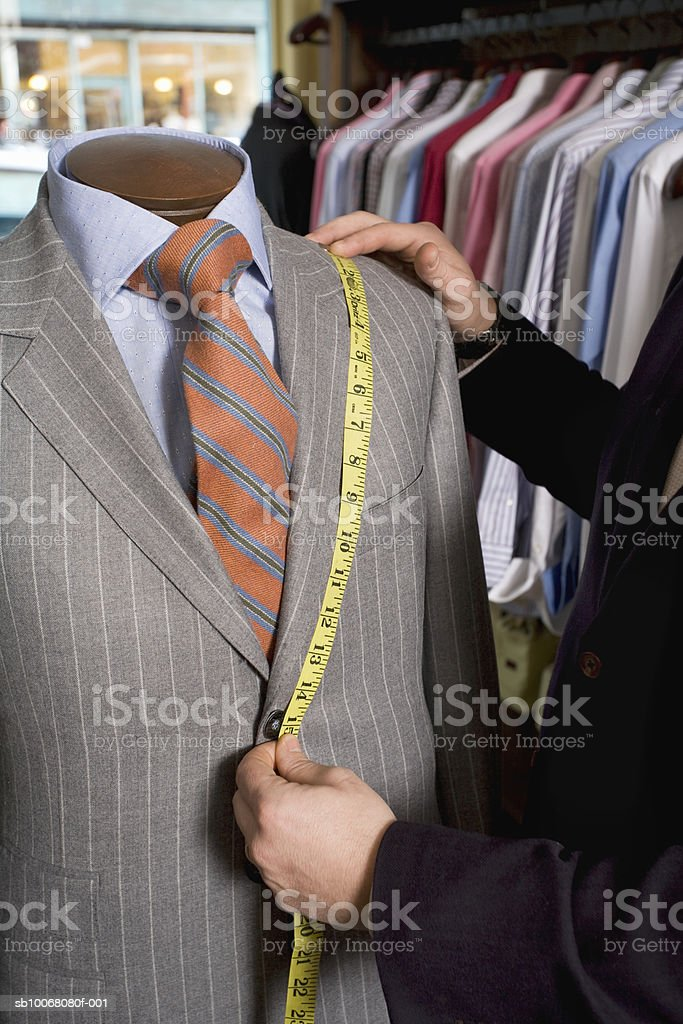 Tailor measuring jacket on dressmaker's model foto de stock libre de derechos