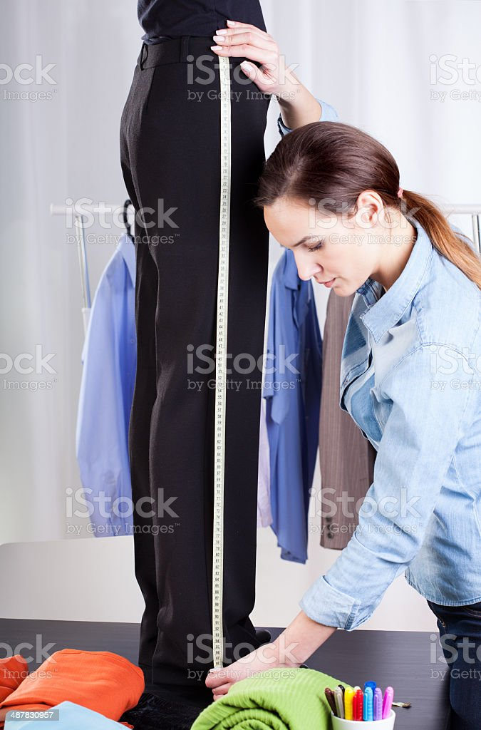 Tailor measuring pant suit stock photo