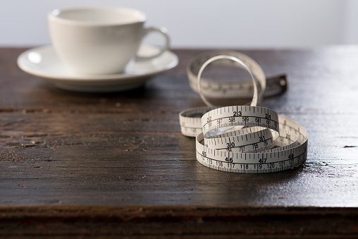istock Tailor measuring tape on wooden table  with a cup of coffee background 873409890