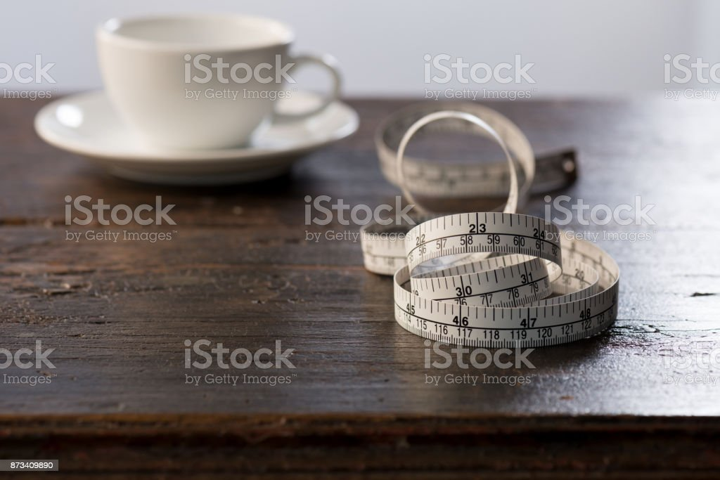 Tailor measuring tape on wooden table  with a cup of coffee background stock photo