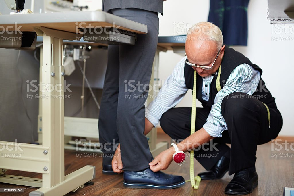 Tailor measuring trousers length stock photo