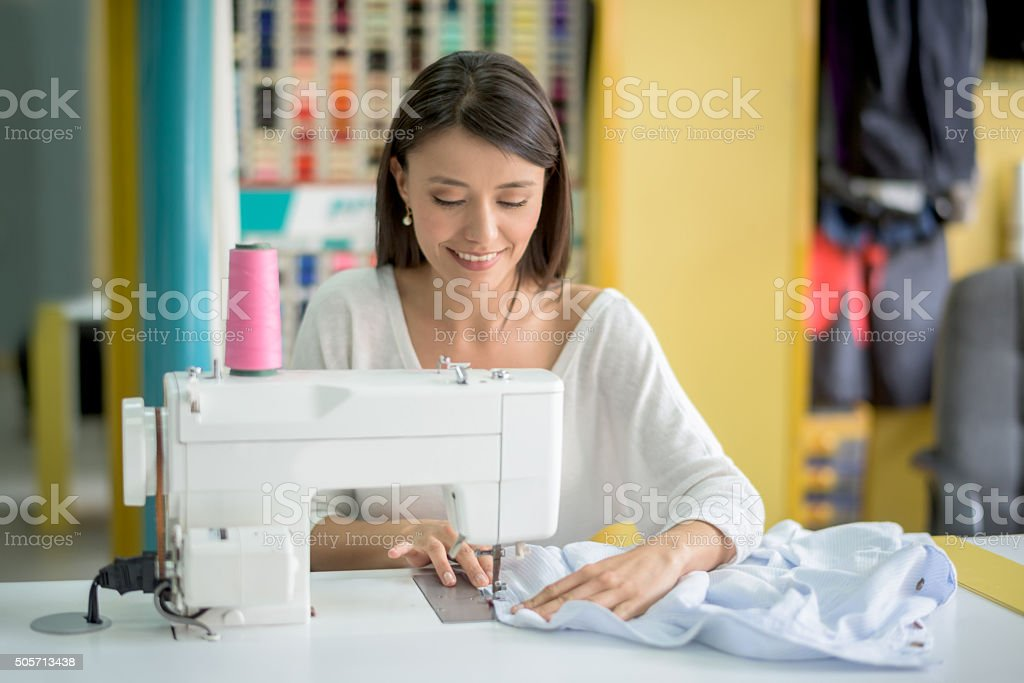 Tailor sewing clothes stock photo
