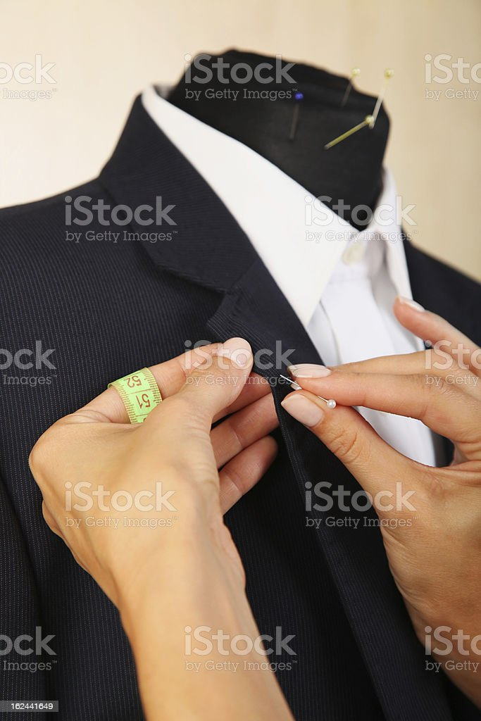 Tailor sewing the collar of a black suit stock photo