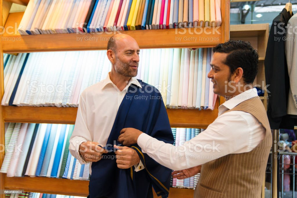 Tailor showing customer fabric samples for his custom made suit royalty-free stock photo