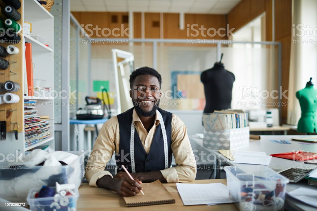 Tailor sketching Young cheerful fashion designer sitting by table in his workshop and making new sketches in notepad Adult Stock Photo